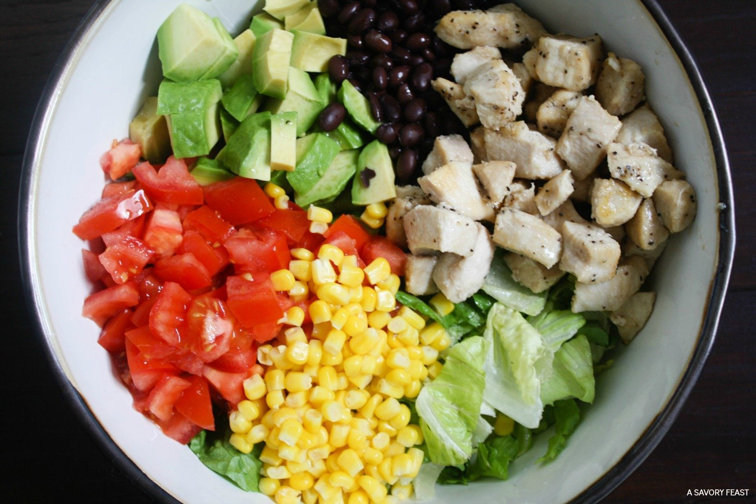 Bright, beautiful and packed with flavor! This nutritious, one dish dinner idea is a family favorite for busy nights. Southwest Salad combines lots of veggies like avocados, tomatoes, and corn with black beans, chicken and a homemade greek yogurt dressing!