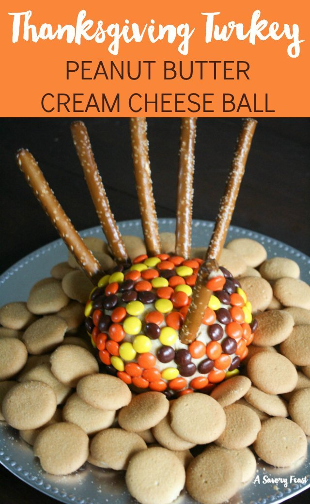 This is the cutest Thanksgiving appetizer! Your guests will gobble up this Thanksgiving Turkey Peanut Butter Cheeseball. A sweet ball of cream cheese and peanut butter covered with Reese's Pieces and decorated to look like a turkey. Serve with pretzels and Nilla Wafers for a sweet appetizer or dessert.