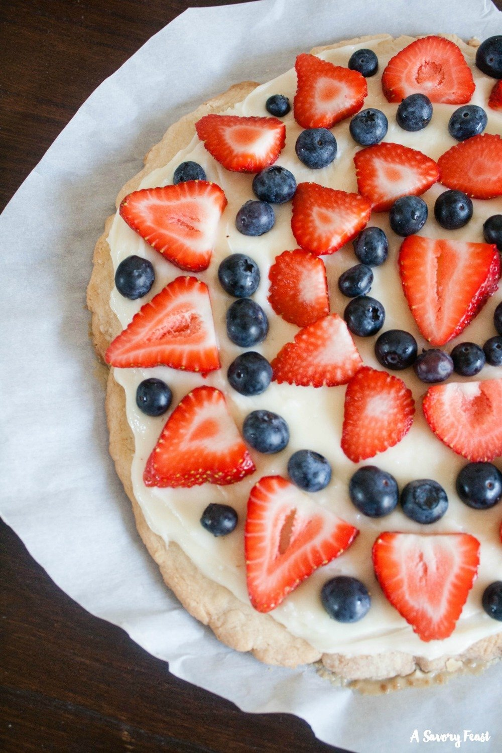 Try this patriotic treat for your 4th of July party! This twist on fruit pizza features an egg free sugar cookie crust topped with a simple cream cheese frosting. Strawberries and blueberries are the finishing touch on this red, white and blue dessert.