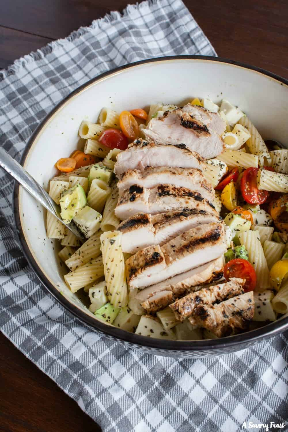 Summer Tomato and Avocado Pasta Salad served with grilled chicken.