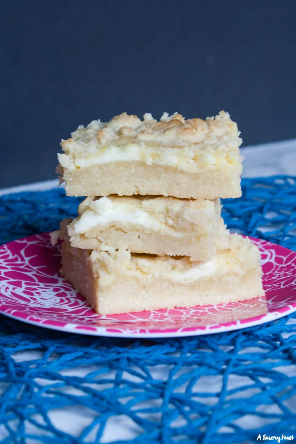 Three layers make up these delicious Lemon Cheesecake Crumble Bars. First comes a shortbread base, then a lemon cheesecake layer. It's all topped with a buttery crumble that brings the whole dessert together. This treat is a must this summer!