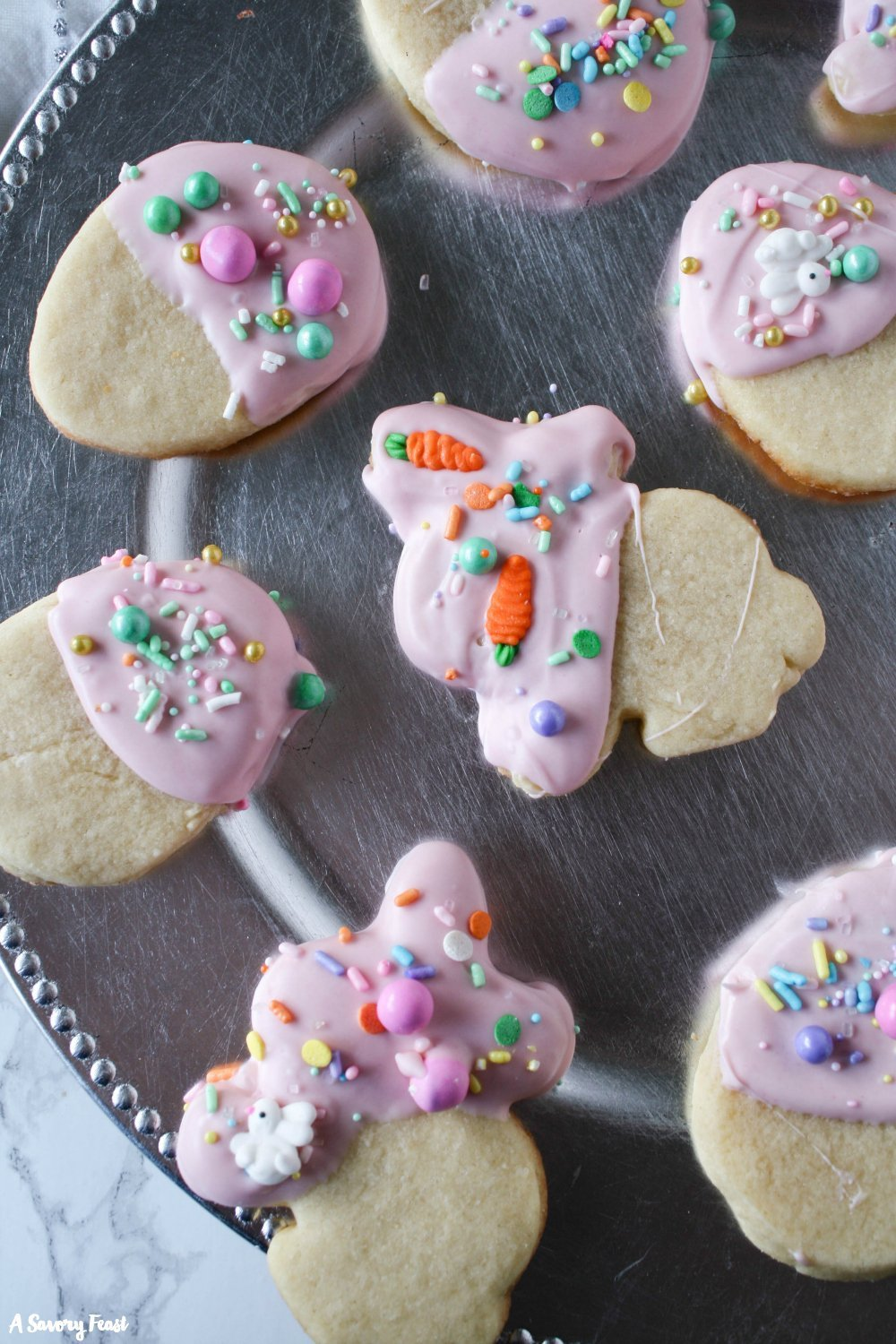 The sweetest cookies to make for Easter this year! Easter White Chocolate Dipped Sugar Cookies start with a classic sugar cookie that is cut into cute Easter shapes such as eggs and bunnies. The cookie is dipped into melted white chocolate and topped with Easter sprinkles!