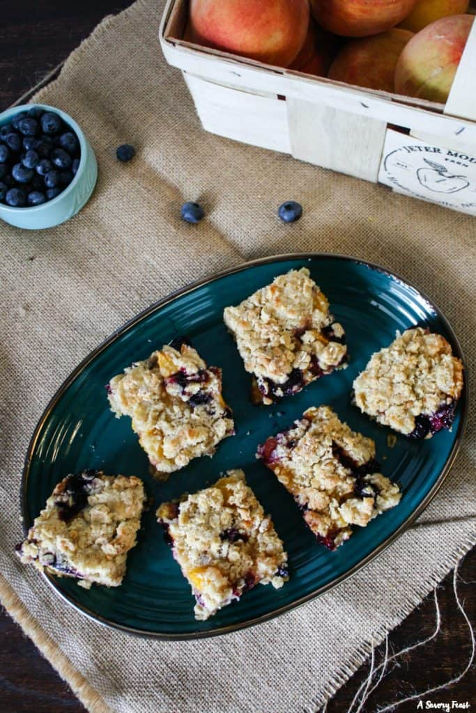 Slices of Blueberry Peach Crumb Bars for a Summer treat.